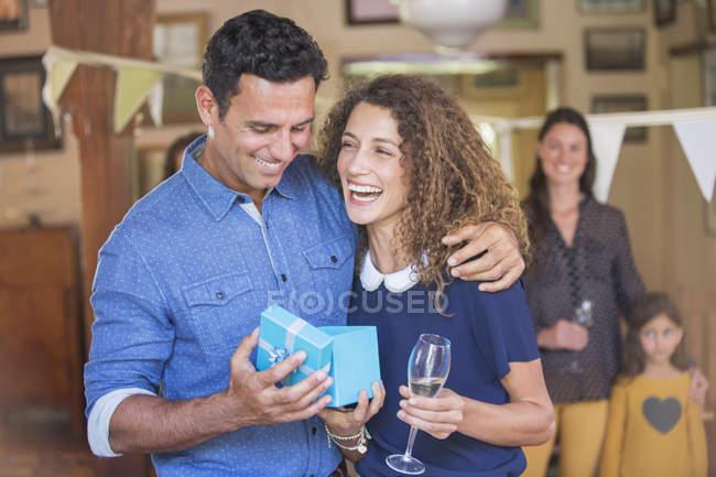 Счастливая прекрасная пара открытие подарок вместе — стоковое фото