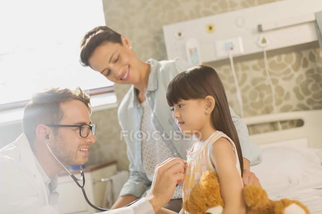 Мужской доктор с помощью стетоскопа на больная в больничной палате — стоковое фото