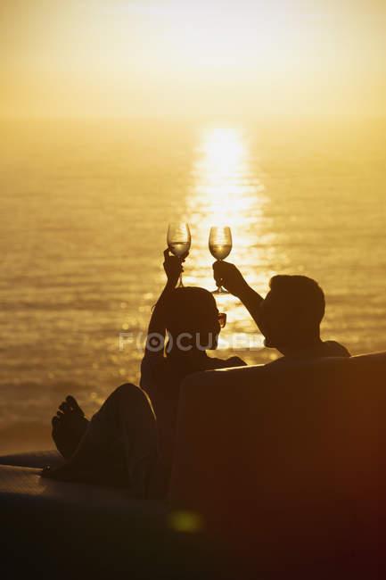 Силуэт пара поджаривания бокалы на балкон с видом на тихий закат океан — стоковое фото