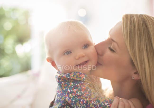 Madre la mejilla de la niña besos - foto de stock