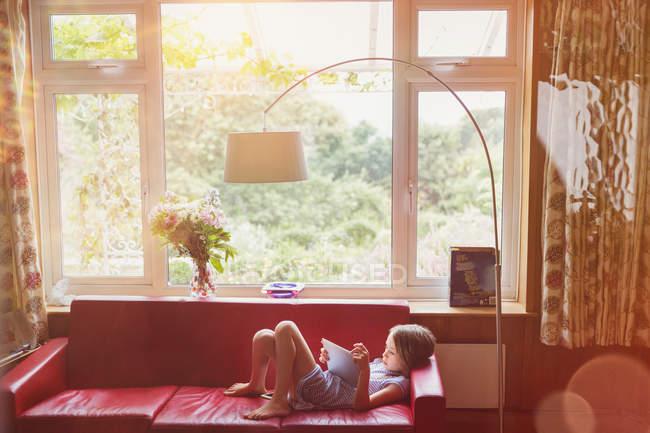 Хлопчик читання, використовуючи цифровий планшетний вітальні-диван — стокове фото