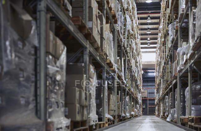 Cajas de cartón apiladas en los estantes de almacén de distribución de mercancías - foto de stock