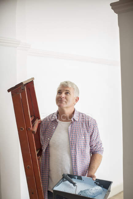 Man carrying ladder and paint tray — Stock Photo