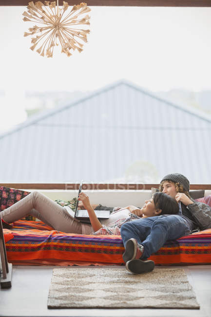 Young couple relaxing using laptop at window — Stock Photo