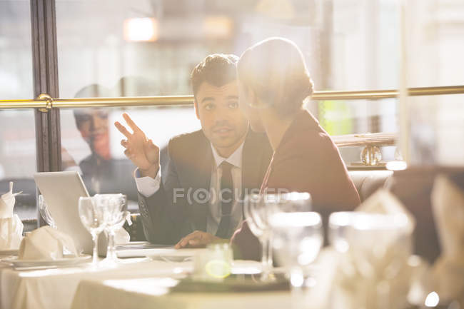 Giovani uomini d'affari che parlano in ristorante — Foto stock