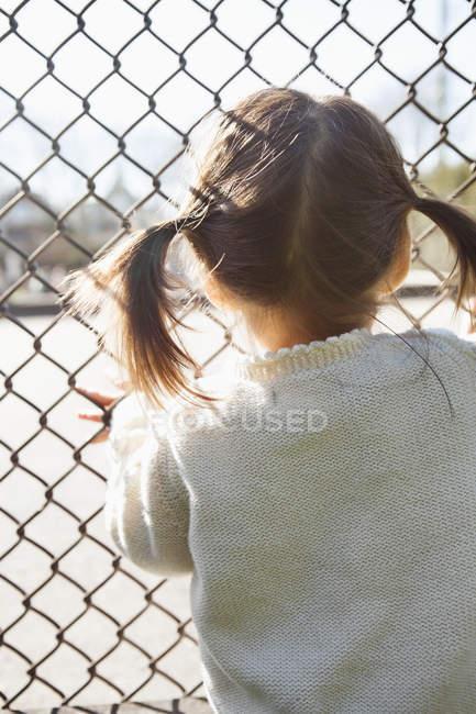 Menina de pé na cerca do elo da cadeia — Fotografia de Stock