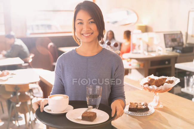 Portrait smiling waitress carrying tray with cappuccino, brownie and water in cafe — Stock Photo