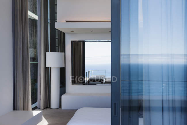 Glass door and windows of modern house overlooking ocean — Stock Photo