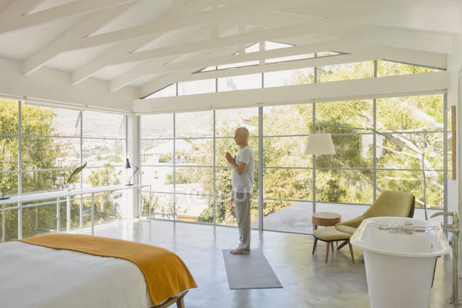 Mature man practicing yoga with hands at heart center in modern bedroom with vaulted wood beam ceilings — Stock Photo