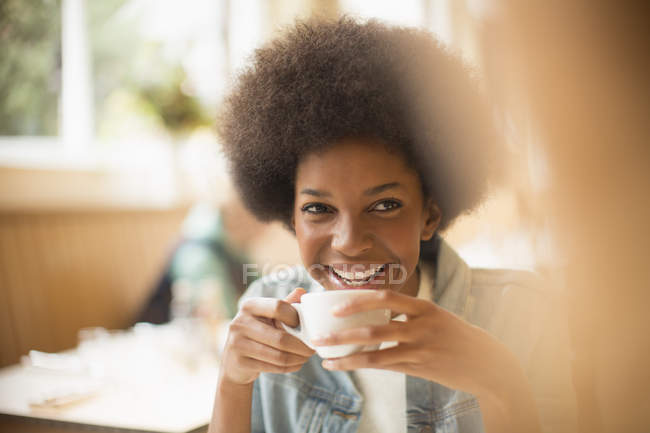 Happy young woman drinking coffee in cafe — Stock Photo