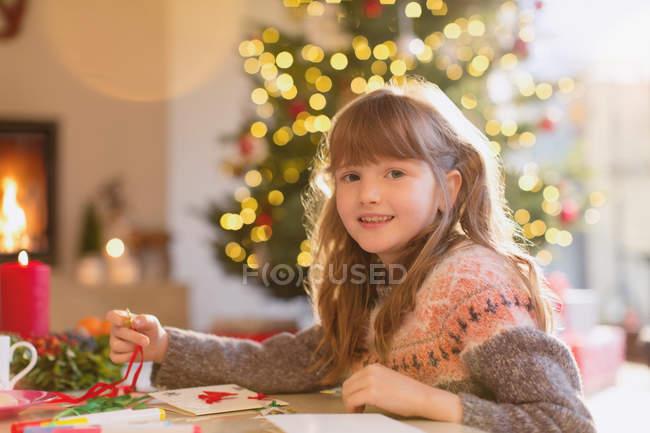 Portrait smiling girl making Christmas decorations — Stock Photo
