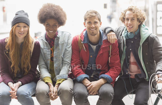 Happy young friends smiling on urban bench — Stock Photo