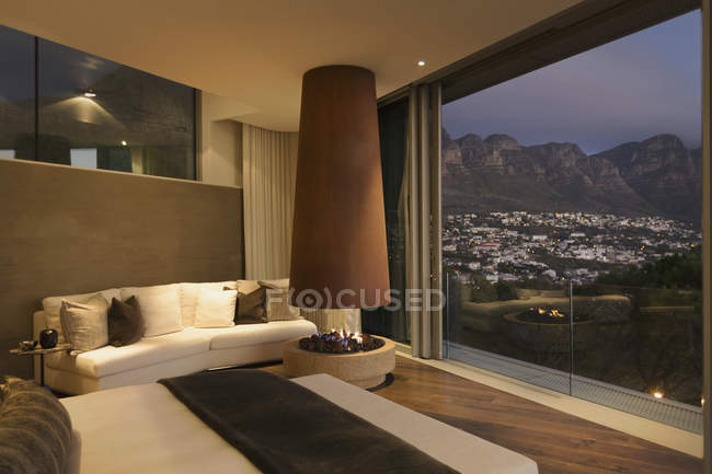 Modern luxury fireplace and home showcase bedroom with mountain and city view — Stock Photo