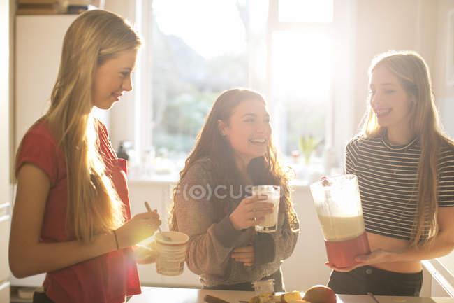Teenage girls making smoothie in sunny kitchen — Stock Photo