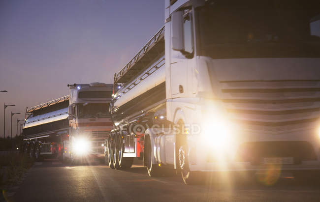 Stainless steel milk tankers in queue at night — Stock Photo