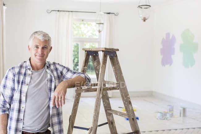 Older man smiling near ladder in livingroom — Stock Photo