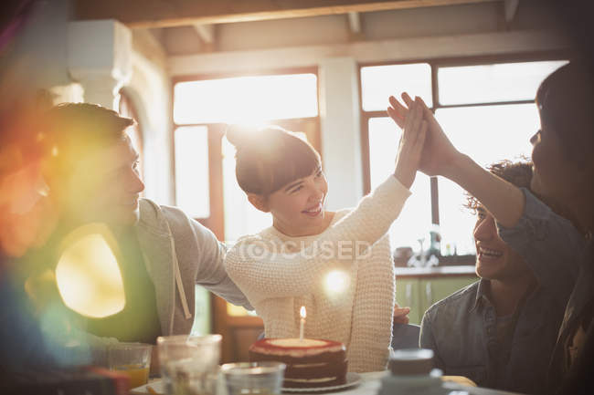 Young friends celebrating birthday with cake and candle high-fiving — Stock Photo