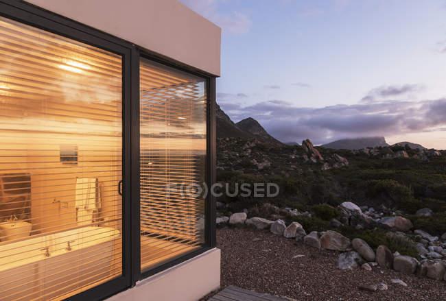 Beleuchtete home Schaufenster Bad unter schroffen Landschaft in der Abenddämmerung — Stockfoto