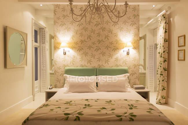 Luxury bedroom with illuminated sconces — Stock Photo
