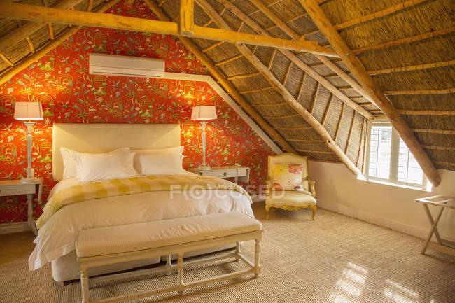 Luxury attic bedroom under wooden roof — Stock Photo