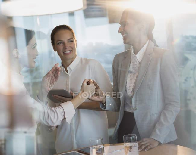 Businesswomen laughing, handshaking in office meeting — Stock Photo