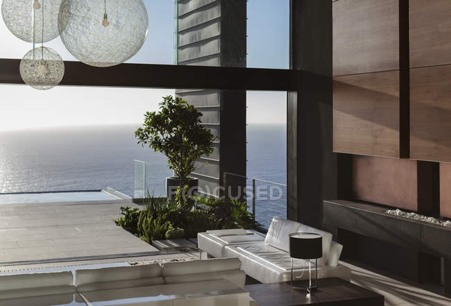 Sofás e mesas na moderna sala de estar com vista para o mar — Fotografia de Stock