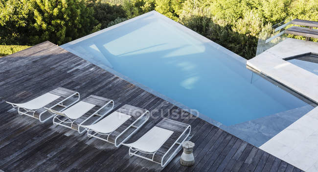 Modern, luxury deck with lounge chairs and swimming pool — Stock Photo