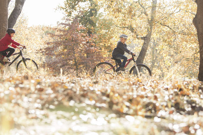 Boy and girl bike riding in woods with autumn leaves — Stock Photo