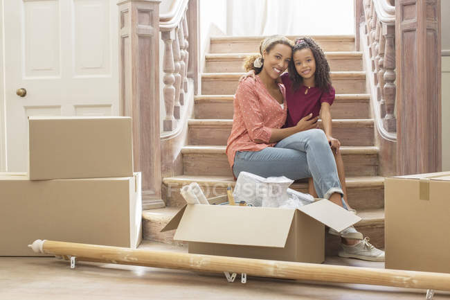 Mother and daughter hugging on stairs — Stock Photo