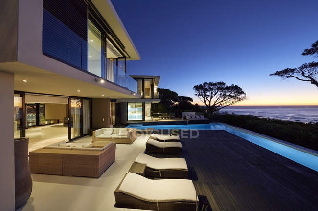 Modern luxury home showcase patio with illuminated swimming pool at dusk — Stock Photo