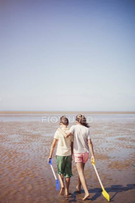 Brother and sister with shovels hugging and walking in wet sand on sunny summer beach below blue sky — Stockfoto