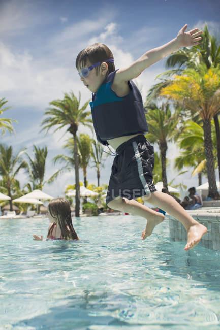 Garçon sautant dans la piscine tropicale ensoleillée — Photo de stock
