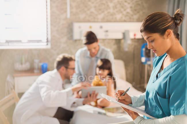Krankenschwester macht sich Notizen auf Klemmbrett für Krankenakte, während Arzt Patientin im Krankenhaus digitales Tablet zeigt — Stockfoto