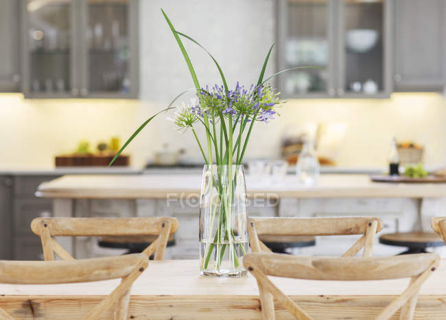 Flowers in vase on wooden table — Stock Photo