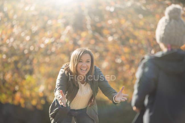 Mère enthousiaste atteignant son fils dans le parc d'automne — Photo de stock