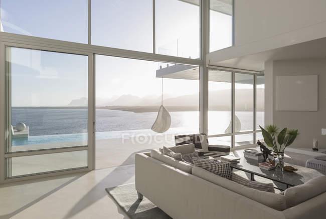 Sunny, tranquille maison de luxe moderne vitrine salon intérieur avec vue sur l'océan — Photo de stock