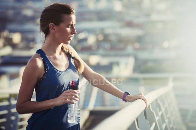 Бегунья с бутылкой воды, отдыхающая на солнечном городском мосту — стоковое фото