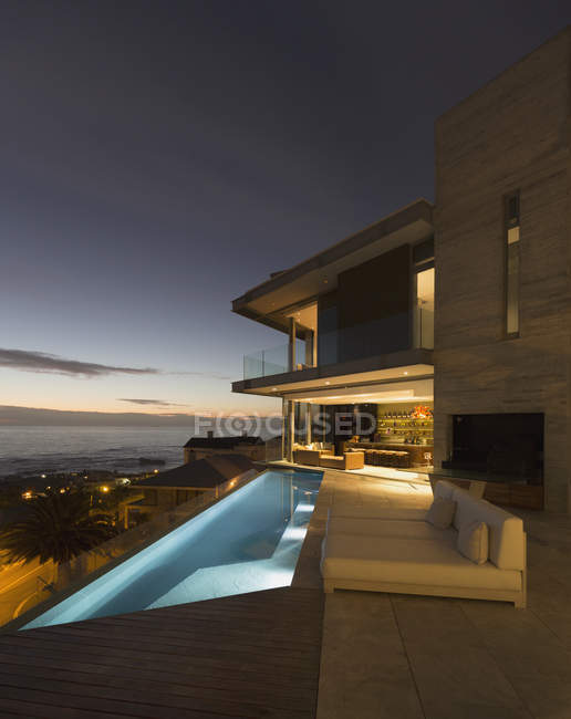 Illuminated home showcase exterior patio with lap pool and ocean view — Stock Photo