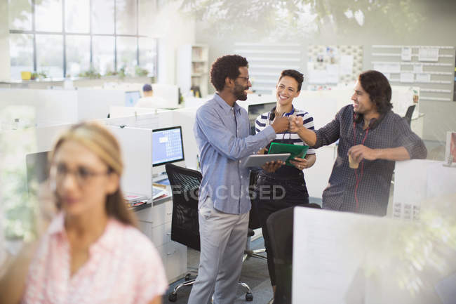 Excited creative business people fist bumping, celebrating in office — Stock Photo