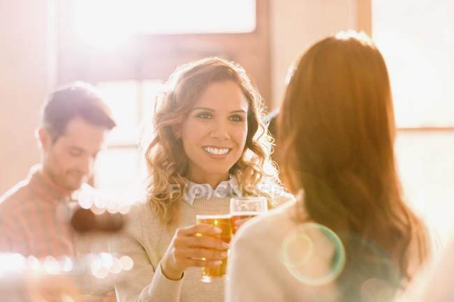 Посміхаючись знайомим жінкам тост пиво келихи у Сонячний бар — стокове фото