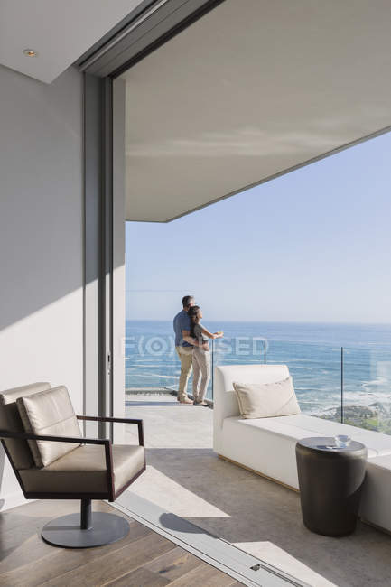 Couple enjoying sunny ocean view from luxury home showcase balcony — Stock Photo