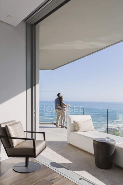 Pareja disfrutando de soleada vista al mar desde el balcón de lujo casa escaparate - foto de stock