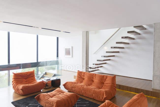 Диваны и лестница в современной гостиной — стоковое фото