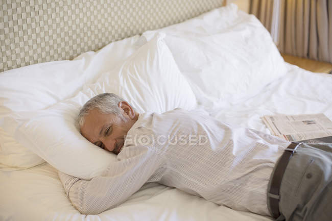 Businessman laying on bed in hotel room — Stock Photo