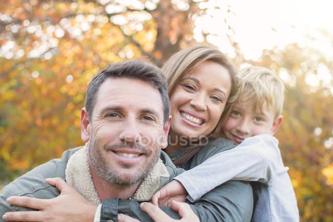 Retrato sonriente familia abrazándose delante de las hojas de otoño - foto de stock