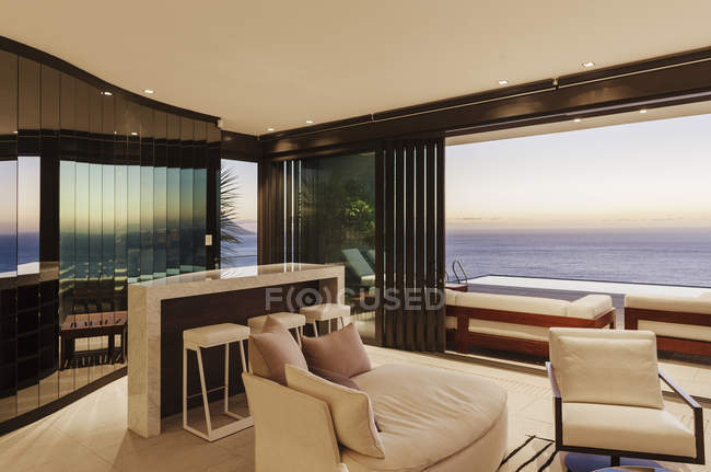 Modern living room and bar overlooking ocean at sunset — Stock Photo