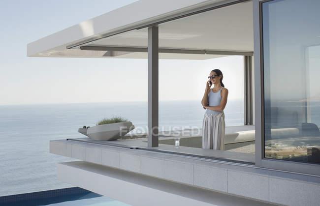 Donna che parla al telefono cellulare sul moderno, lusso casa vetrina patio esterno con vista sull'oceano — Foto stock