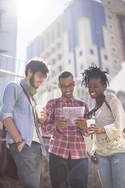 Друзья, использующие цифровой планшет на городской улице — стоковое фото