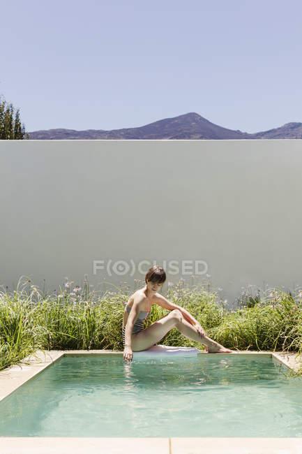 Donna seduta ai margini della piscina di lusso — Foto stock