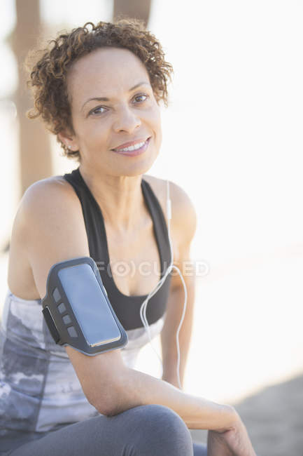 Portrait of confident female jogger wearing arm band — Stock Photo
